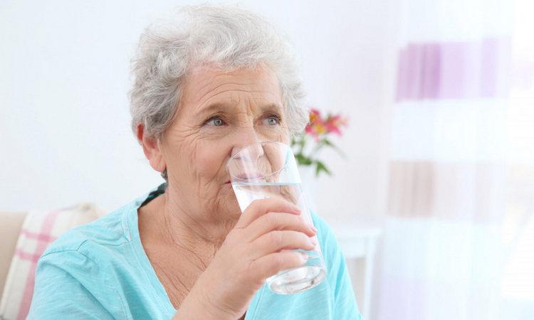 Пожилая женщина пьет воду